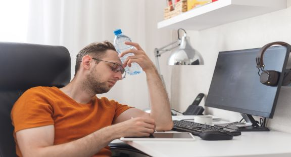 Man working from home exhausted from heat